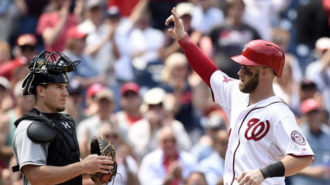 Washington Nationals right fielder Bryce Harper, right, responds to the crowd as he crosses home plate after hitting a home run in front of Miami Marlins catcher J.T. Realmuto, left, during the third inning of their baseball game at Nationals Park in Washington, Wednesday, May 6, 2015. This was Harper's second home run of the game. (AP Photo/Susan Walsh)