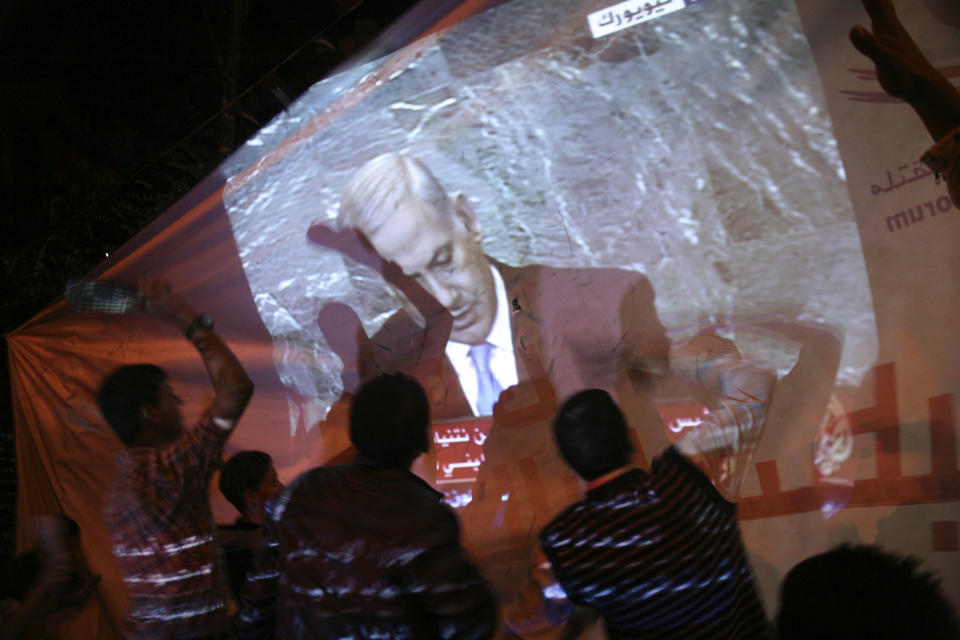 Palestinians hold up shoes as they watch  live footage of Israeli Prime Minister Benjamin Netanyahu's speech at the United Nations General Assembly in New York,  in West Bank city of Hebron. Friday, Sept. 23, 2011. (AP Photo/Nasser Shiyoukhi)