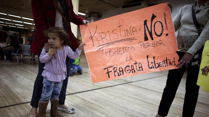 "Relatives of members of the crew of Argentine tall ship Libertad hold a banner reading in Spanish ""Kirstina we cant's loose the frigate Libertad"" referring to Argentina's President Cristina Fernandez in Buenos Aires airport, Argentina, Thursday, Oct. 25, 2012.  Nearly 300 navy cadets arrived to Argentina's capital from Ghana on an Air France charter hired by the government after Argentina's President Cristina Fernandez refused to negotiate the release of the Argentine naval sailing ship, Libertad. The ship had been held in a port outside Ghana's capital Oct. 2, when a Ghana court ruled to detain the vessel as collateral for Argentina's unpaid debts. (AP Photo/Natacha Pisarenko)"