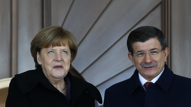 Turkish Prime Minister Davutoglu shakes hands with German Chancellor Merkel during a welcoming ceremony in Ankara