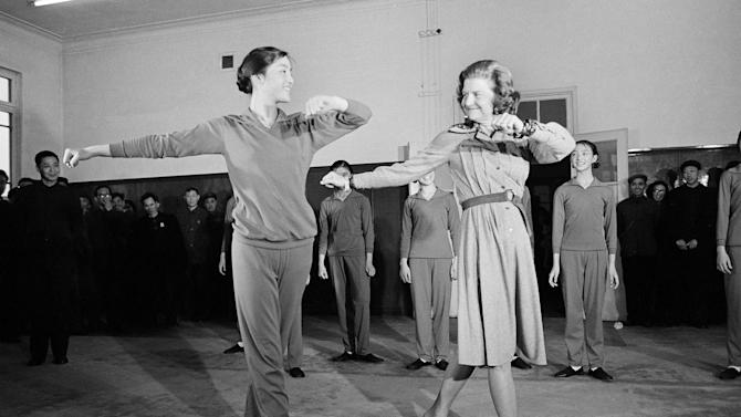 FILE - In this Dec. 3, 1975 file picture, first lady Betty Ford performs an unscheduled dance with an unidentified teacher, left, in front of a group of students at a Peking dance school. Betty Ford, the former first lady whose triumph over drug and alcohol addiction became a beacon of hope for addicts and the inspiration for her Betty Ford Center, has died, a family friend said Friday, July 8, 2011. She was 93. (AP Photo/Bob Daugherty)