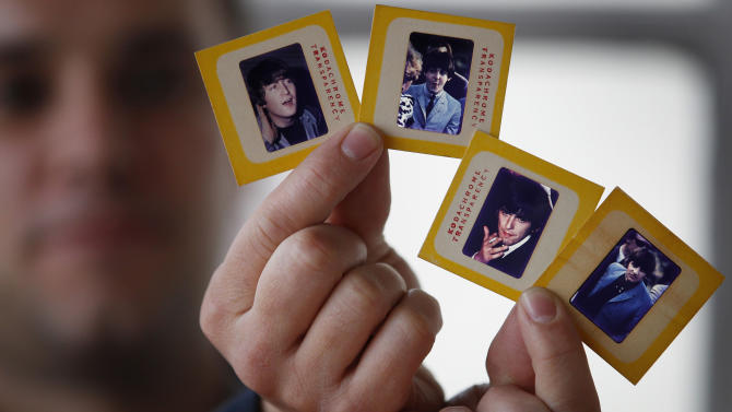 In this photo taken Dec. 29, 2012, auctioneer Paul Fairweather holds four colour transparencies of The Beatles taken during their first tour of the USA in 1964. The rare colour transparencies, taken by Dr. Robert Beck, are to be sold along with the copyright at Omega Auctions in Stockport, England, in a special Beatles memorabilia auction in March 2013. The unpublished collection of 65 slides contain many stage shots.(AP Photo/PA,Dave Thompson) UNITED KINGDOM OUT