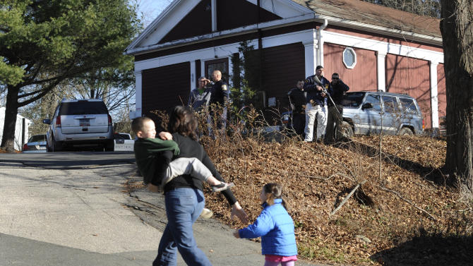 FILE - In this Friday, Dec. 14, 2012 file photo, a mother runs with her children as police above canvass homes in the area following a shooting at the Sandy Hook Elementary School in Newtown, Conn., where Adam Lanza fatally shot 27 people, including 20 children. Psychiatrists say after the grief and fear fades, most of Newtown's young survivors probably will cope without long-term emotional problems, often through play. Among the challenges will be spotting which children are struggling enough that they may need professional help. (AP Photo/Jessica Hill, File)