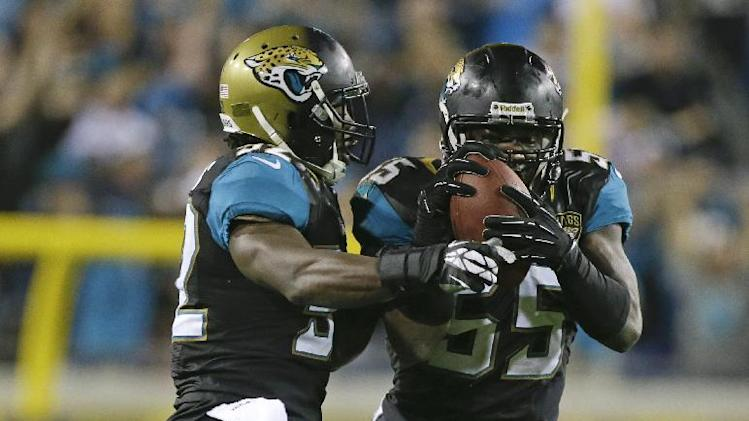 Jacksonville Jaguars outside linebacker Geno Hayes, right, celebrates an intercepted pass with teammate J.T. Thomas during the final moments of an NFL football game against the Houston Texans in Jacksonville, Fla., Thursday, Dec. 5, 2013. Jacksonville Jaguars won the game 27-20