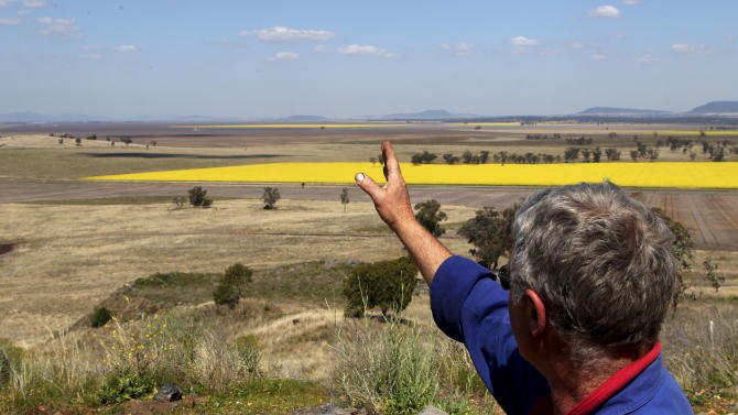 In this Sept. 11, 2012 photo, farmer Tony Clift points past bright yellow canola crops towards the location of a proposed coal mining site near Gunnedah, Australia, 450 kilometers (280 miles) northwest of Sydney. Shenhua Watermark, a subsidiary of state-owned China Shenhua Energy, the world's biggest coal mining company, spent 167 million Australian dollars (more than $170 million) to buy 43 farms covering 36,300 acres. Gunnedah's former mayor says sellers told him Shenhua paid several times market value. Clift's family has plowed the rich black soil of Australia's Liverpool Plains for six generations. The thought of selling never crossed his mind - until the Chinese company came to town. (AP Photo/Rob Griffith)