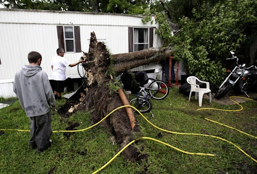 Allen Michael Reynolds, left, and his brother, David Anthony Reynolds look at the roots of a tree that fell onto their home during Tropical Storm Andrea on Thursday, June 6, 2013 in Gainesville, Fla. Both brothers were inside when the tree fell and only suffered a few scratches.  Tropical Storm Andrea, the first named storm of the Atlantic season, hammered Florida with rain, heavy winds, and tornadoes Thursday as it moved over land toward the coast of Georgia and the Carolinas, promising sloppy commutes and waterlogged vacation getaways through the beginning of the weekend. (AP Photo/The Gainesville Sun, Matt Stamey)  THE INDEPENDENT FLORIDA ALLIGATOR OUT