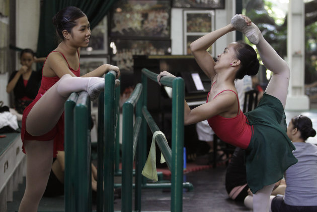 In this photo taken Nov. 25, 2012, Filipino slum dweller Jessa Balote, right, talks with another student as she stretches before the start of classes at Ballet Manila in the Philippine capital. Balote