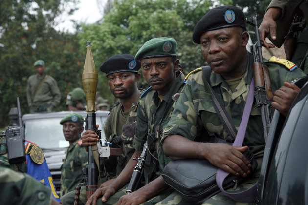 Congolese government soldiers (FARDC) patrol the streets of Minova under their control Sunday Nov. 25, 2012. Government troops remain in Minova, 25 kilometers (15 miles) south of Sake, following a failed attack on M23 last Thursday.Regional leaders meeting in Uganda called for an end to the advance by M23 rebels toward Congo's capital, and also urged the Congolese government to sit down with rebel leaders as residents fled some towns for fear of more fighting between the rebels and army. (AP Photo/Jerome Delay)