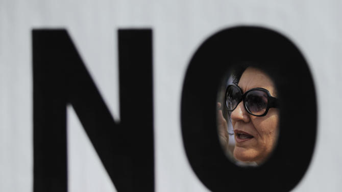 A protestor is seen through a banner as she shouts slogans during a demonstration against government-imposed austerity measures and labor reforms in the public healthcare sector in Madrid, Spain, Sunday, July 21, 2013. Thousands of Madrid residents and medical workers angered by budget cuts and plans to part privatize their cherished national health service protested on the streets Sunday. (AP Photo/Andres Kudacki)