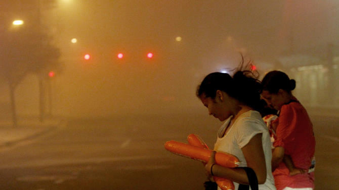 Pedestrians cross a street as they try to get out of a dust storm as it moves though downtown Phoenix, Tuesday, July 5, 2011. (AP Photo/Ross D. Franklin)