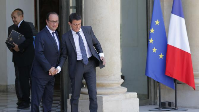 French President Hollande escorts Prime Minister Valls as he leaves the Elysee Palace in Paris following the weekly cabinet meeting
