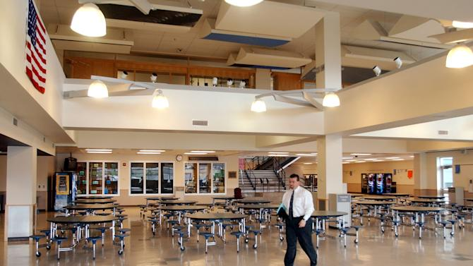 "FILE - This April 14, 2004 file photo shows Rick Kauffman, a spokesman for Jefferson County Schools, walking through the cafeteria at Columbine High School in Littleton, Colo. The library, that was once above the cafeteria, was removed after the tragedy at the school and a new one built. Many changes were made at the school after the shootings. After the massacre at Columbine, students finished the year at another school. Columbine reopened in time for the following school year after extensive repairs. ""The intent of the school district is to put this back as a high school,"" Jack Swanzy, lead architect on the refurbishing project, said at the time. ""We don't want to make it a shrine to the tragedy.""  (AP Photo/Ed Andrieski, File)"