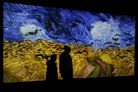 "The shadow of a journalist is cast on the projection of the painting ""Champ de Ble aux Corbeaux"" by painter Vincent van Gogh during the exhibition ""Van Gogh/Artaud The Man Suicided by Society"" in Paris"