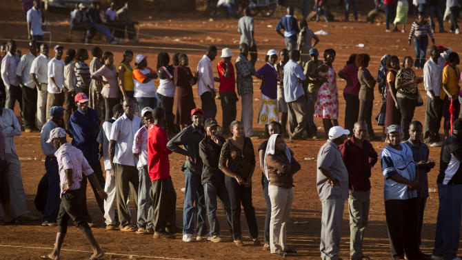 Voters who had waited in line for many hours queue at sunset to vote at a polling station in Githurai, north of Nairobi, in Kenya, Monday, March 4, 2013. Five years after more than 1,000 people were killed in election-related violence, Kenyans went to the polls on Monday to cast votes in a nationwide election seen as the country's most important - and complicated - in its 50-year history. (AP Photo/Ben Curtis)
