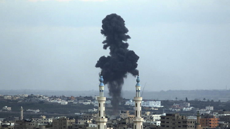 Smoke rises behind a mosque's minarets after an Israeli missile strike in Gaza City, northern Gaza Strip, Friday, July 18, 2014. Israeli troops pushed deeper into Gaza on Friday to destroy rocket launching sites and tunnels, firing volleys of tank shells and clashing with Palestinian fighters in a high-stakes ground offensive meant to weaken the enclave's Hamas rulers. (AP Photo/Hatem Moussa)