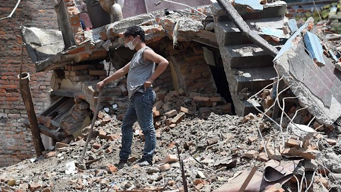 A Nepalese resident clears debris from his damaged house in the Balaju suburb of Kathmandu, on April 27, 2015