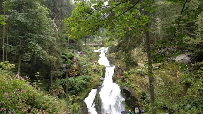 This Sept. 3, 2014 photo shows people walking near a waterfall in Triberg, Germany. The Black Forest got its name from a canopy of leaves so dense that parts of the woods are dark. It also inspired Grimm Brothers' fairy tales. (AP Photo/Siobhan Starrs)