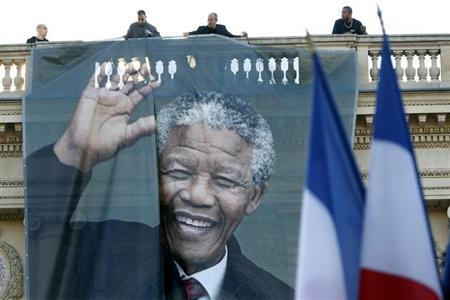 Workmen unfurl a giant banner with a photo of the late South African President Mandela to cover the facade of the Quai d'Orsay Foreign Affairs Ministry in Paris