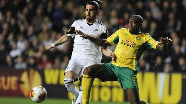 Swansea City's Chico Flores (L) is challenged by Kuban Krasnodar's Djibril Cisse during their Europa League soccer match at the Liberty Stadium in Swansea, Wales, October 24, 2013. REUTERS