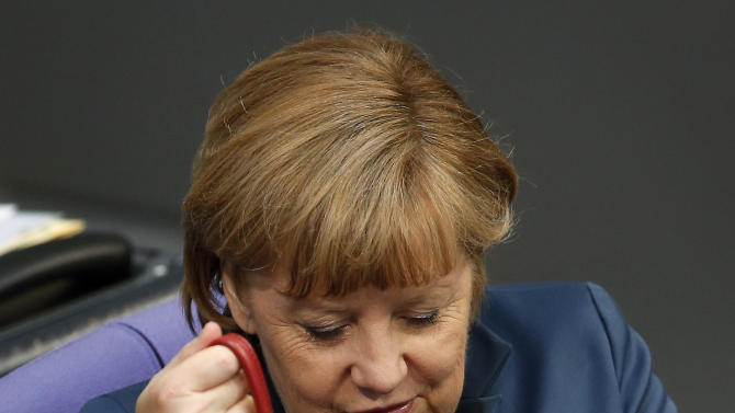 German Chancellor Angela Merkel looks into her handbag during a meeting of the German federal parliament, Bundestag, on the EU financial assistance for Cyprus in Berlin, Germany, Thursday, April 18, 2013. (AP Photo/Michael Sohn)