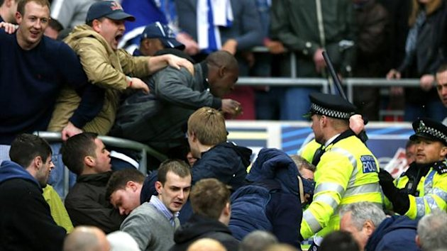Millwall fans fight themselves and the police during their FA Cup semi-final with Wigan at Wembley (Reuters)