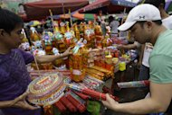 A Filipino man buys firecrackers at a makeshift stand in downtown Manila, Philippines on Saturday Dec. 31, 2011. More than 200 people have been injured by illegal firecrackers and celebratory gunfire in the Philippines despite a government scare campaign against reckless holiday revelries, officials said. (AP Photo/Aaron Favila)