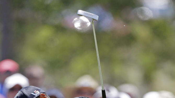 Tiger Woods raises his club after making an eagle putt on the second hole during the second round of The Players championship golf tournament at TPC Sawgrass, Friday, May 10, 2013 in Ponte Vedra Beach, Fla. (AP Photo/John Raoux)
