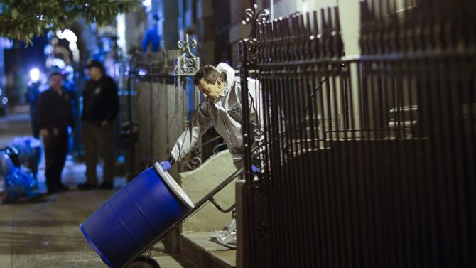 """A member of a cleaning crew with """"Bio Recovery Corporation"""" pushes a barrel to be loaded in a truck of Centers for Disease Control and Prevention after cleaning the apartment where Dr. Craig Spencer lives in New York"""