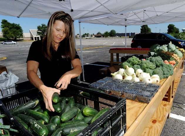 FILE - In this June 13, 2012 file photo, Julie Trunnell, with Trunnell's Farm Market, unloads cucumbers along with other locally grown produce in the parking lot at Towne Square Mall, in Owensboro, Ky