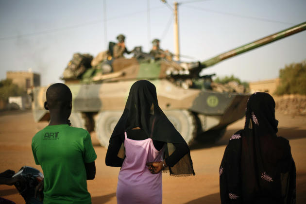 Malian teenagers watch a convoy of French military vehicles pass through Gao, northern Mali, Tuesday Feb. 19, 2013. A French soldier has been confirmed dead during a military operation in northern Mal