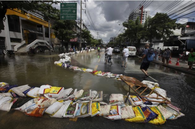 Floodwater gushes into a manhole in the middle of a street in Bangkok, Thailand, Saturday, Oct. 29, 2011. Defenses shielding the center of Thailand's capital from the worst floods in nearly 60 years m