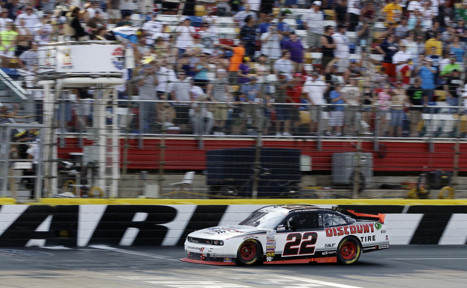 Brad Keselowski takes the checkered flag to win the NASCAR Nationwide Series History 300 auto race in Concord, N.C., Saturday, May 26, 2012. (AP Photo/Chuck Burton)