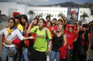 Supporters of Venezuela's late President Hugo Chavez protest over others cutting the line as they wait to view his body in state at the Military Academy in Caracas, March 7, 2013. REUTERS/Tomas Bravo