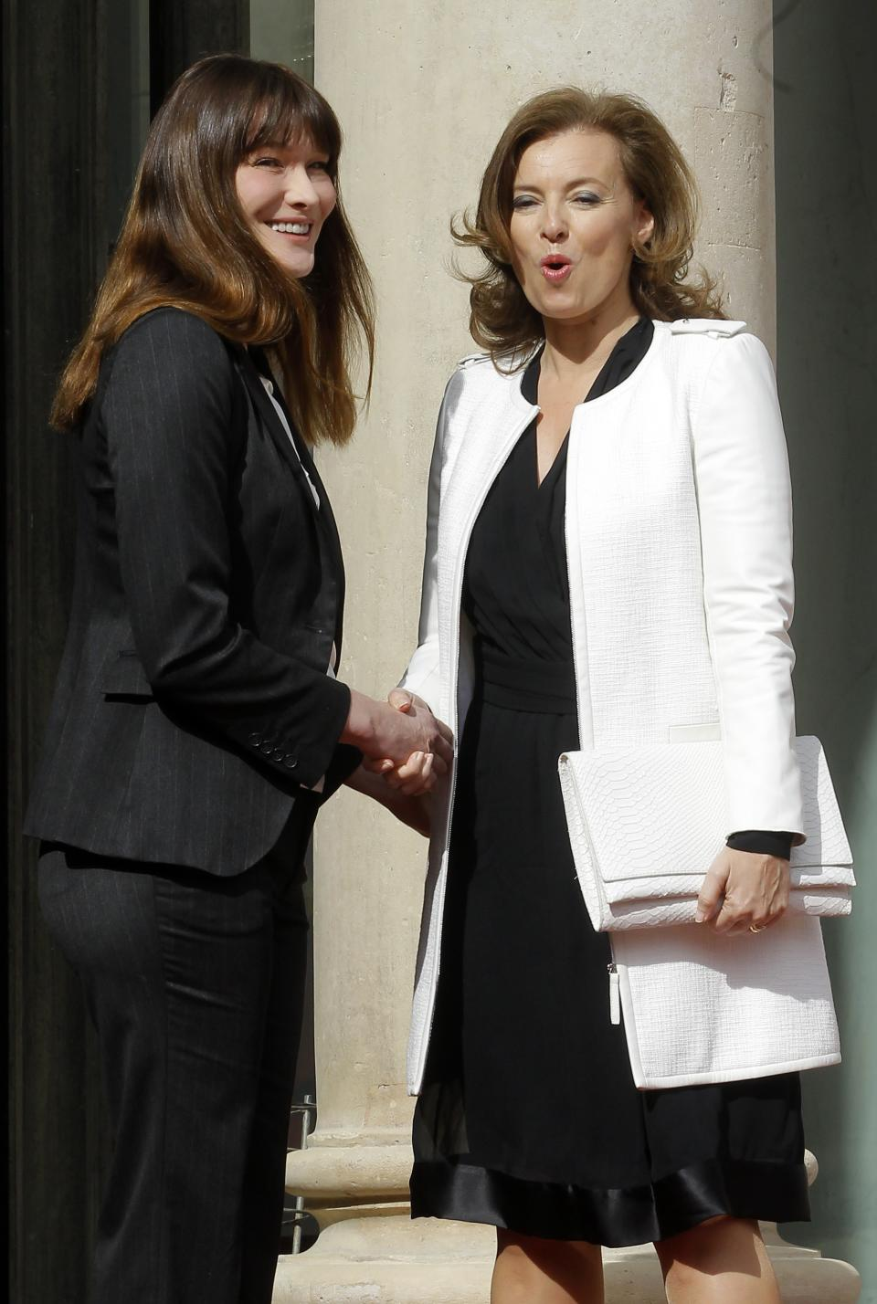 French President-elect Francois Hollande's companion Valerie Trierweiler, right, shakes hands with outgoing President Nicolas Sarkozy's wife Carla Bruni-Sarkozy before the presidential handover ceremony, Tuesday, May 15, 2012 at the Elysee Palace in Paris.  (AP Photo/Jacques Brinon)