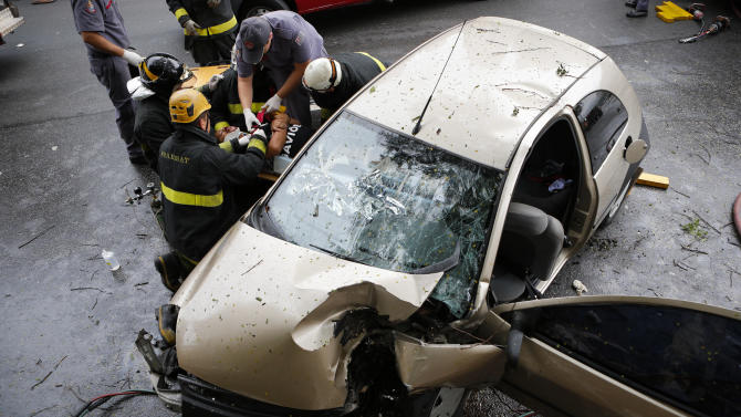In this Nov. 25, 2012 photo, rescue workers remove a man from a Ford Ka vehicle after an accident in Sao Paulo, Brazil. Three men were injured when they lost control of their car on one of Sao Paulo's main avenues on a rainy morning. The Ford Ka hatchback sold in Europe scored a high safety rating of four out of five stars when it was tested by Euro NCAP in 2008; its Latin American version scored one star. Ford acknowledged that particular Ka is built on an outdated platform, and said it cannot be compared with the European version of the same name. (AP Photo/Victor R. Caivano)