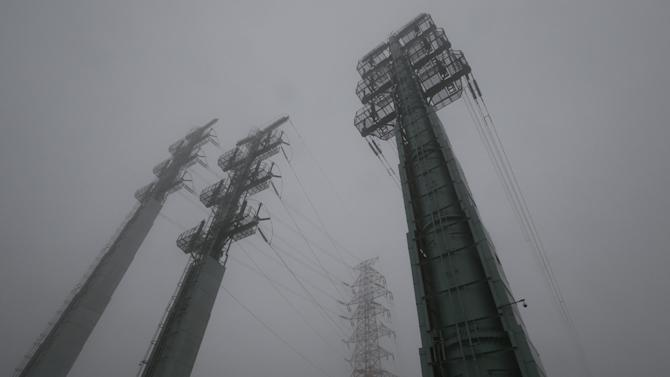 Transmission towers supplying power to the Kaesong Industrial Complex from South Korea, are seen on a foggy and rainy day after South Korea cut off power, in Paju, South Korea, Friday, Feb. 12, 2016. South Korea has cut off power and water supplies to a factory park in North Korea, officials said Friday, a day after the North deported all South Korean workers there and ordered a military takeover of the complex that had been the last major symbol of cooperation between the rivals. (AP Photo/Lee Jin-man)