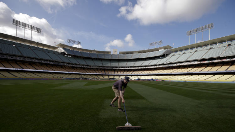 A worker brooms the grass before a season-opening baseball game between the Los Angeles Dodgers and the San Francisco Giants in Los Angeles, Monday, April 1, 2013. (AP Photo/Jae C. Hong)
