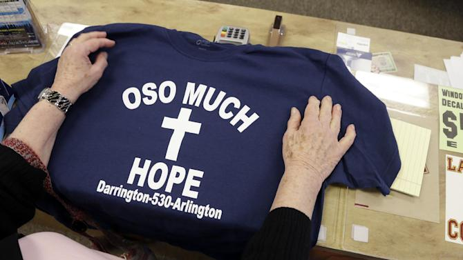 A customer rests her hands on a tee-shirt for sale at a sporting goods store with proceeds to be directed to victims of a deadly landslide Friday, March 28, 2014, in Arlington, Wash. The death toll from the mudslide in nearby Oso, Wash., is expected to rise considerably within the next two days as the Snohomish County Medical Examiner's Office catches up with the recovery effort, Snohomish County District 21 Fire Chief Travis Hots said Thursday. (AP Photo/Elaine Thompson)