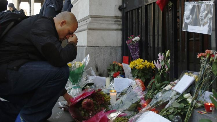 A man pays respect in front of floral tributes left for former South African President Nelson Mandela at the South African High Commission in London