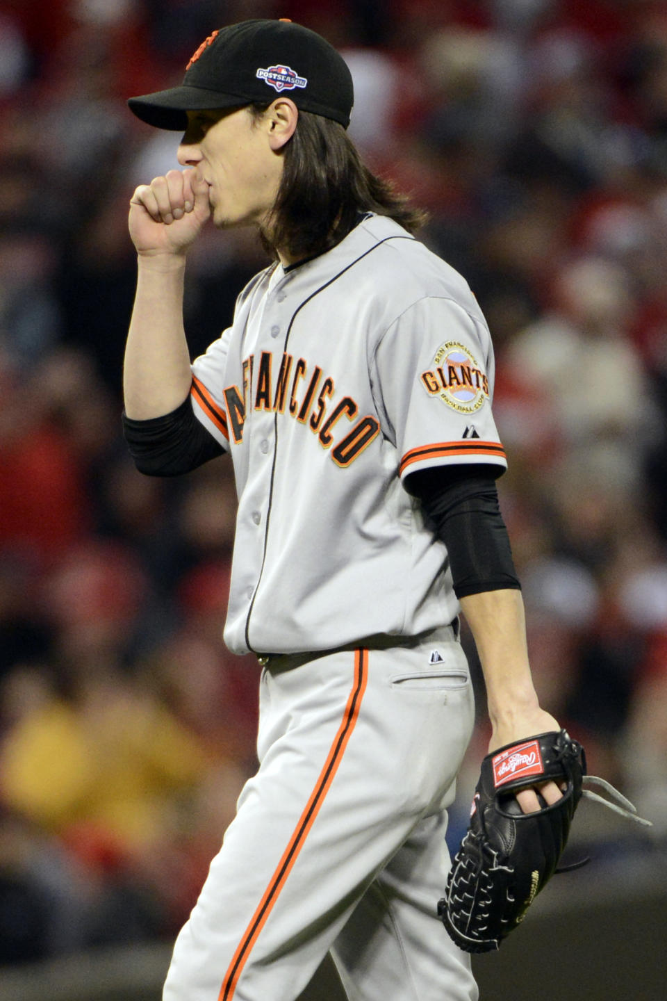 San Francisco Giants relief pitcher Tim Lincecum blows on his hands in the eighth inning of Game 4 of the National League division baseball series against the Cincinnati Reds, Wednesday, Oct. 10, 2012, in Cincinnati. Lincecum was the winning pitcher in the game won by the Giants 8-3. (AP Photo/Michael Keating)