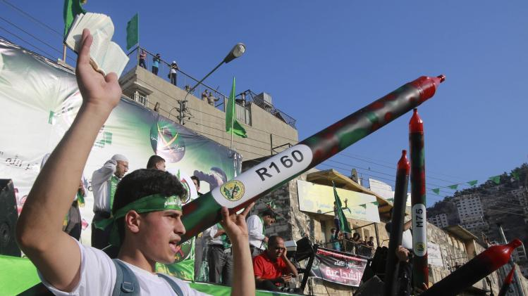 A Palestinian Hamas supporter holds a mock rocket and a copy of the Koran during a rally in the West Bank city of Nablus