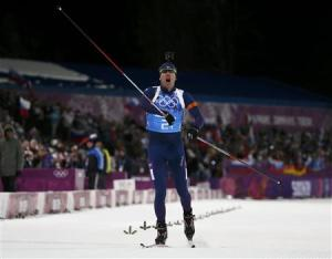 Norway's Svendsen celebrates as he crosses the finish line to win mixed biathlon relay at 2014 Sochi Olympic Games