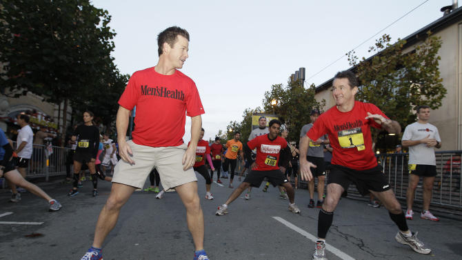 Celebrity host Billy Bush, left, and Men's Health Publisher Ronan Gardiner, right, warming up at the starting line of the Men's Health Urbanathlon, Sunday, November 18, 2012 in San Francisco. The Men's Health Urbanathlon is a rigorous 9 mile course, packed with challenging urban obstacles set against the backdrop of iconic city landmarks.(Photo by Tony Avelar/Invision for Men's Health/AP Images)