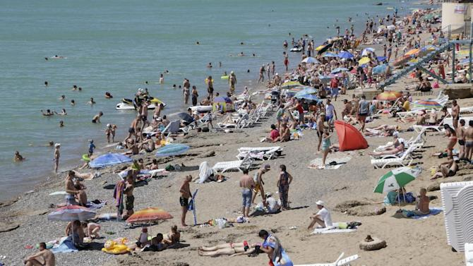 File picture shows rourists enjoying the sun by the seaside on a beach some 40km from the Crimean capital Simferopol, on June 29, 2014