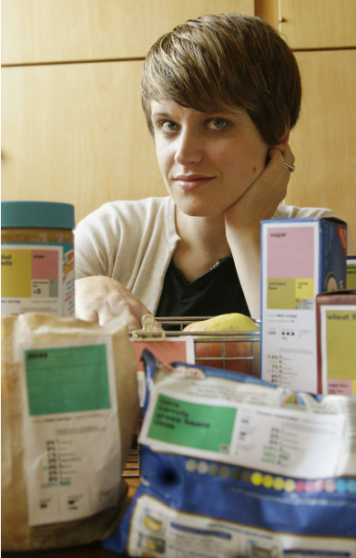 "EDS: ADDS DETAILS FOR SUBJECT - ADVANCE FOR MONDAY SEPT. 5 - This Aug. 10, 2011 photo shows designer Renee Walker, winner of the Rethink the Food Label contest, posing for a photograph next to her food label samples in San Francisco. Nutrition and design experts want to overhaul the ""nutrition facts"" panel found on packaged foods to make it easier to understand what a food's value is _ and hopefully, make healthier choices."
