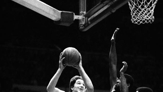 FILE - In this March 7, 1985, file photo, St. John's University's Chris Mullin,left, goes up for a basket as Providence's Keith Lomax, center and Ray Knight defend, during their Big East tournament game at New York's Madison Square Garden. Mullin, St. John's all-time leading scorer and still the face of its basketball program three decades after his career ended, has agreed to coach the Red Storm, a person with knowledge of the discussions told The Associated Press on Monday, March 30, 2015. The person spoke on condition of anonymity because there was no formal announcement.(AP Photo/Ray Stubblebine, File)