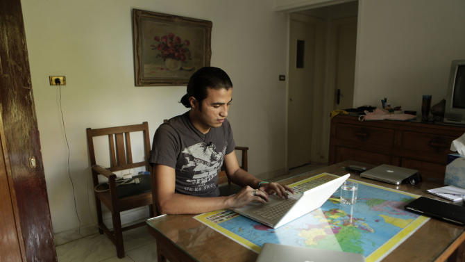 FILE - In this Tuesday, Aug. 28, 2012 file photo, Mohammad B., a refugee from Daraa, Syria, looks at video from the day he was shot by Syrian government forces, in Cairo, Egypt. The U.N. refugee agency says the number of Syrian refugees who have fled their country's civil war to find shelter in Egypt has now topped 150,000 a significant jump from last month's figure of 95,000. (AP Photo/Maya Alleruzzo, File)