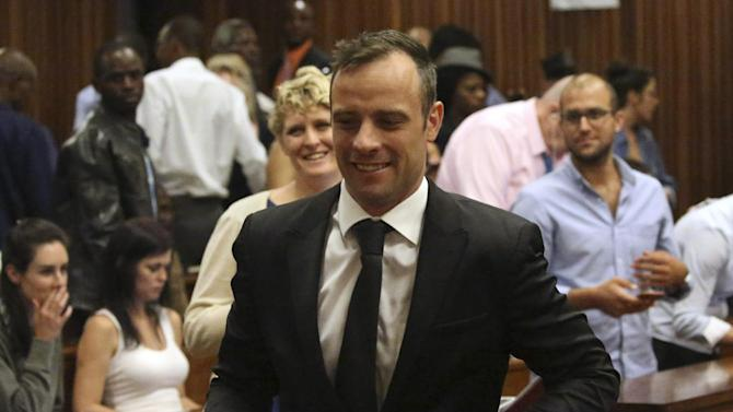 Oscar Pistorius, center, leaves a courtroom of the High Court in Pretoria, South Africa, Tuesday Dec. 8, 2015. Judge Aubrey Ledwaba granted Pistorius bail and extended his house arrest for the murder conviction of his girlfriend Reeva Steenkamp until April 18 2016. (AP Photo/Siphiwe Sibeko, Pool)