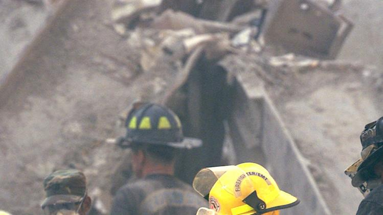 In this Sept. 13, 2001 photo, a  first responder works in the rubble of the former World Trade Center in New York. A decade's worth of study has answered only a handful of questions about the hundreds of health conditions believed to be related to the tons of gray dust that fell on the city when the trade center collapsed, from post-traumatic stress disorder, asthma and respiratory illness to vitamin deficiencies, strange rashes and cancer. (AP Photo/Beth Keiser, Pool)
