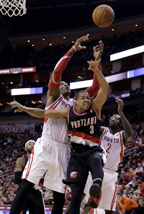 Portland Trail Blazers' C.J. McCollum (3) goes up for a rebound with Houston Rockets' Dwight Howard, left, and Patrick Beverley (2) during the third quarter of an NBA basketball game Sunday, M